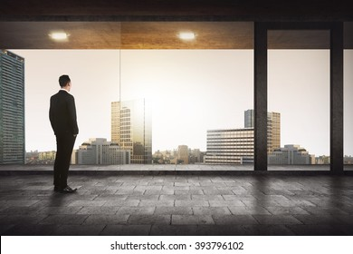 Back view of successful manager looking the city from his office