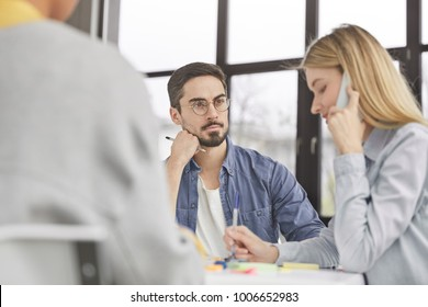 Back view of successful young people collaborate for common aims, discuss something, sit at working table. Blonde busy female has telephone conversation, tries to check or varify her balance.