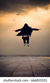 Back View Sunset Young Hipster Guy Jumping Learn to Fly Concept