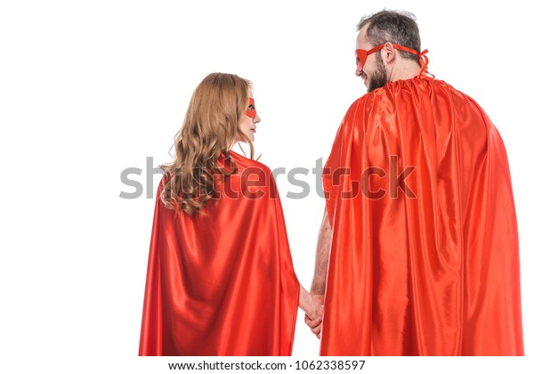 back view of super couple in masks and cloaks holding hands and looking at each other isolated on white
