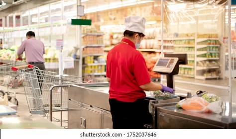 The back view of supermarket worker wearing uniform with surgical glove working at the weight machine for calculate money to customer with the new normal and social distancing concept.
