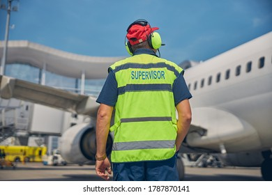 Back view of a supervisor in noise-canceling headset standing in front of a large airliner