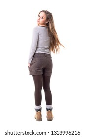 Back view of surprised young woman turning and looking at camera with long flying blonde hair. Full body isolated on white background.