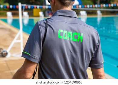 Back view of swimming coach, wearing COACH shirt, walking near swimming pool