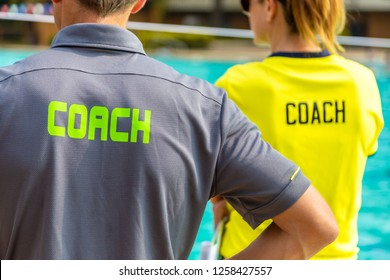 Back view of swimming coaches, wearing COACH shirt, working together at an outdoor swimming pool