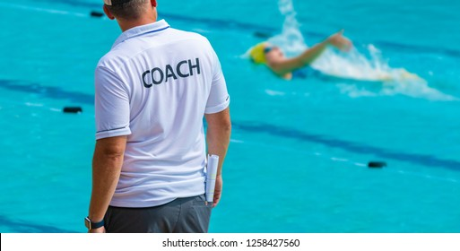 Back view of swimming coaches, wearing COACH shirt watiching his female swimmer doing backstroke at a local outdoor swimming pool