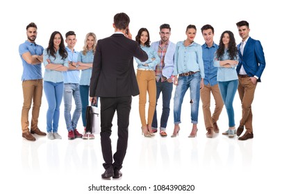 back view of team leader talking on the phone in front of his casual team while holding a black suitcase in hand, on white background