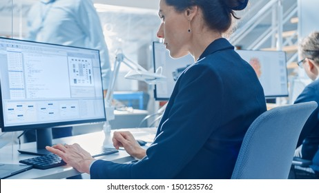 Back View of Team of Technology Engineers Working on Desktop Computers in Bright Office. Screens Show IDE / CAD Software, Implementation of Machine Learning, Neural Networking and Cloud Computing