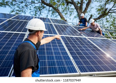 Back view of technician with electrical screwdriver standing in front of unfinished high exterior solar panel photo voltaic system pointing at workers connecting panels to high steel platform.