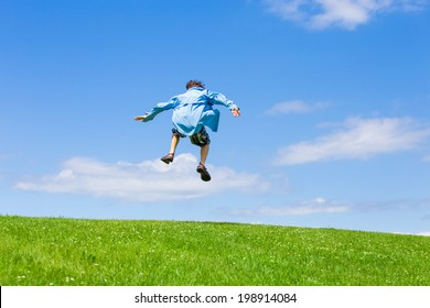 Back view of a teen boy jumping in the air on a sunny summer day.