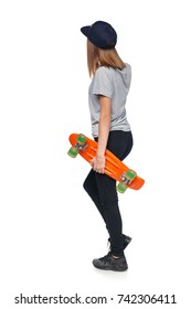 Back view of a teen girl in full length walking holding skate board, isolated on white background