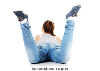 Back view of teen girl lying on her belly on white background
