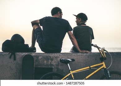 Back view of a teen and his father sitting on a wall with bicycle and skateboard. Young rider and dad relaxing after a fun day of jump and tricks with bmx People waiting friends to go to the skatepark
