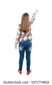 Back view of teenage girl points at wall. Rear view. Isolated on white background