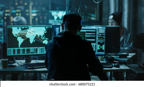 Back View of Teenage Hacker Working in Computer and Infecting with Virus Data Servers of Government Infrastructures. His Hideout is Dark with Many Monitors Around.