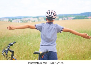Back view of teenager boy in protective helmet spread his arms out like a bird standing next to his bike in park on summer day. Children's outdoor activities in summer.