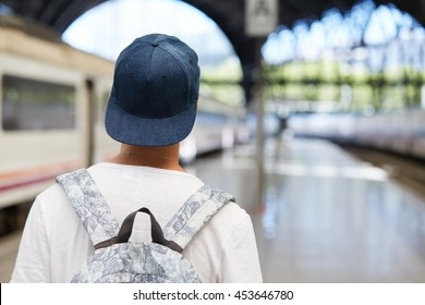Back view of teenager boy in snapback carrying backpack while returning home after classes at school, walking alone against urban background with copy space for your text or advertising content
