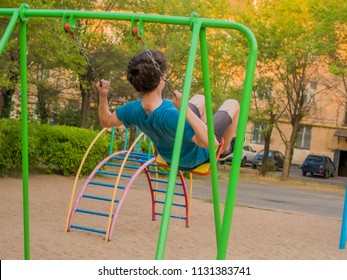 back view of teenager boy swinging on a playing ground