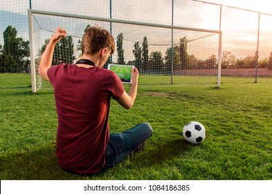 Back view, Teenager sitting on football/soccer field watching the game on tablet, fist in the air, team scored a goal . Soccer world cup, streaming online