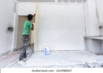 Back view of Thai young painter use paint roller applying color on wall of new building house.