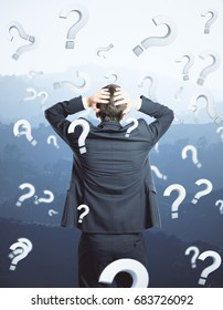 Back view of thinking young businessman on landscape background with question marks. Worried concept