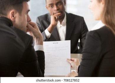 Back view of thoughtful HR managers reading, discussing candidates resume, worried african american job applicant waiting decision at interview on background. Anxiety, Lie, mistakes in questionable CV