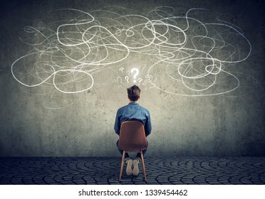 Back view of a thoughtful young businessman sitting on chair looking at a scribble on a wall feeling confused with too many questions