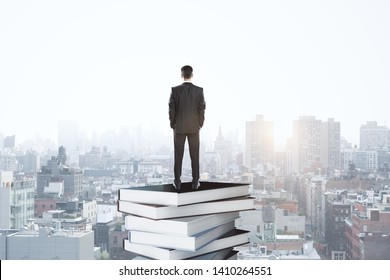 Back view of thoughtful young businessman on rooftop standing on book stack. Bangkok city background. Education and knowledge concept