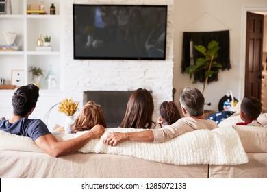Back view of three generation Hispanic family sitting on the sofa watching TV