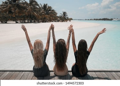 Back view of Three girls sitting on wooden planks on tropical beach Maldives. Girlfriends  having fun, open arms and enjoyment. Slim cute models with healthy long hair at Summer vacations.