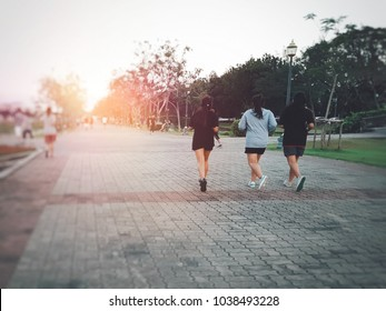 Back view of three sporty women friends running together on the road in the City park against beautiful sunset sky with blurred people exercise, walking and relaxing.