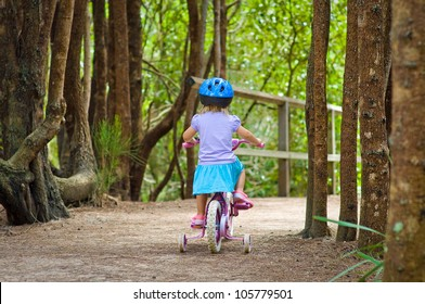 Back view of a toddler girl riding a bike in the forest