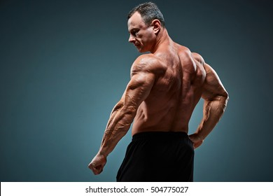 The back view of torso of attractive male body builder on gray background.