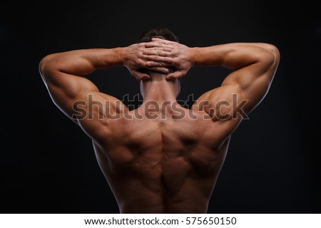The back view of torso of attractive male body builder on dark background.