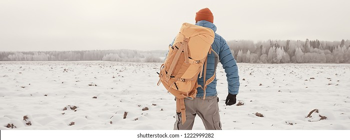back view of  tourist with  backpack hiking in winter in Norway / one man carrying  backpack in a Norwegian winter landscape.