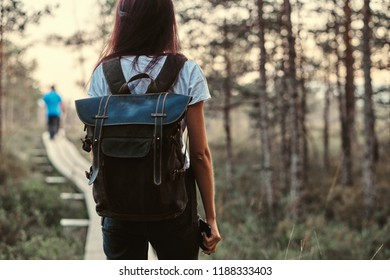 Back view of a tourist girl with backpack walk on a wooden footpath in beautiful forest.