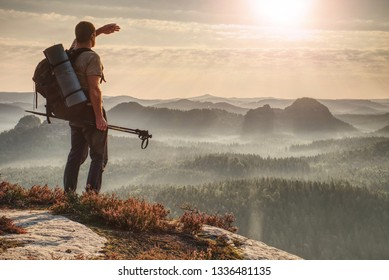 Back view of tourist hiker with backpack walking on mountain big rocks. Orange misty clouds below in valley and glowing yellow orange dramatic morning sky