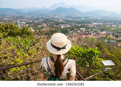 Back view of tourist woman looking to beautiful view of Luang Prabang town from the top of Mt.Phu Si (or Mt.Phou Si) high hill in the centre of the old town of Luang Prabang in Laos.