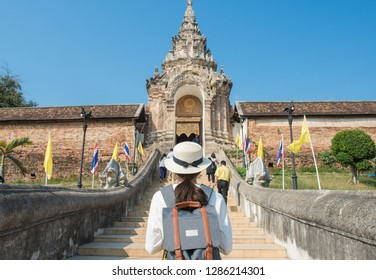 Back view of tourist woman standing in front of the entrance gate to Wat Phra That Lampang Luang an iconic Buddhist temple in Lampang province, Thailand.