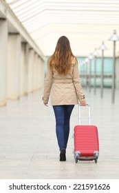 Back view of a tourist woman walking and carrying a suit case in an airport or station
