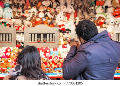 Back view of tourists playing shooting game to win plush toys on the wall at Christmas funfair winter wonderland in London