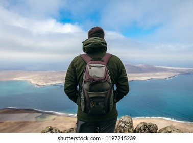 Back view of traveler man enjoying beautiful seascape of La Graciosa Island at viewpoint. Travel concept. Winter in Canary Islands