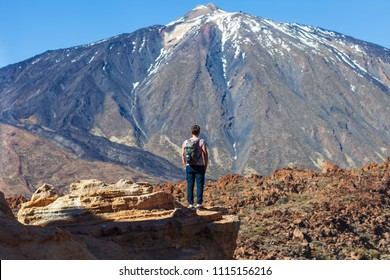 Back view of traveler man standing on the edge of rock looking to volcano El Teide in National park of Tenerife, Canary Islands, Spain. Travel the world