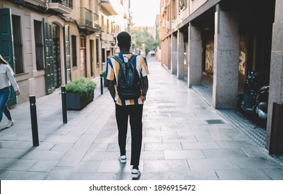 Back view of trendy dressed male student with leather backpack going to university, stylish African American tourist in casual clothes walking at travel city spending vacations for visiting new town