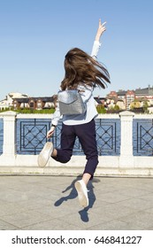 Back view of trendy girl with small backpack posing and jumping on background of waterfront.
