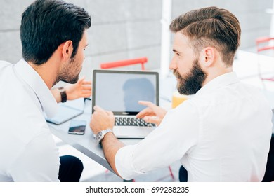back view of two bearded business men young outdoor using computer - remote working, business, marketing concept