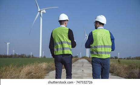 Back view of two engineers discussing against turbines on wind farm while walking along road on sunny day