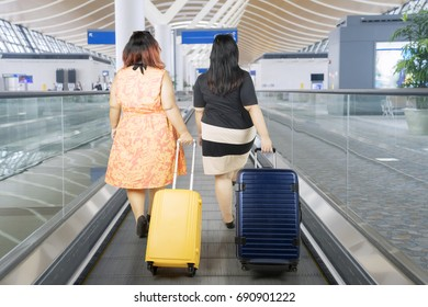 Back view of two fat women carrying a suitcase while walking on the escalator airport