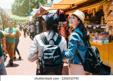 back view of two female tourists visiting the traditional market. beautiful lady looking at the vendor which they walked by. Friendship concept with young people shopping in the holiday market in LA.