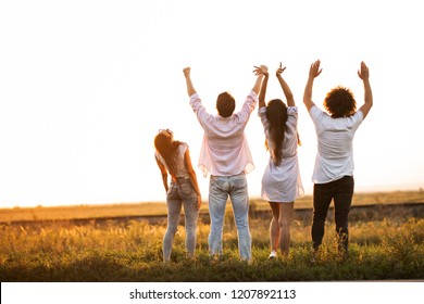 Back view. Two guys and two girls are standing in the field on a summer day and holding their hands up.